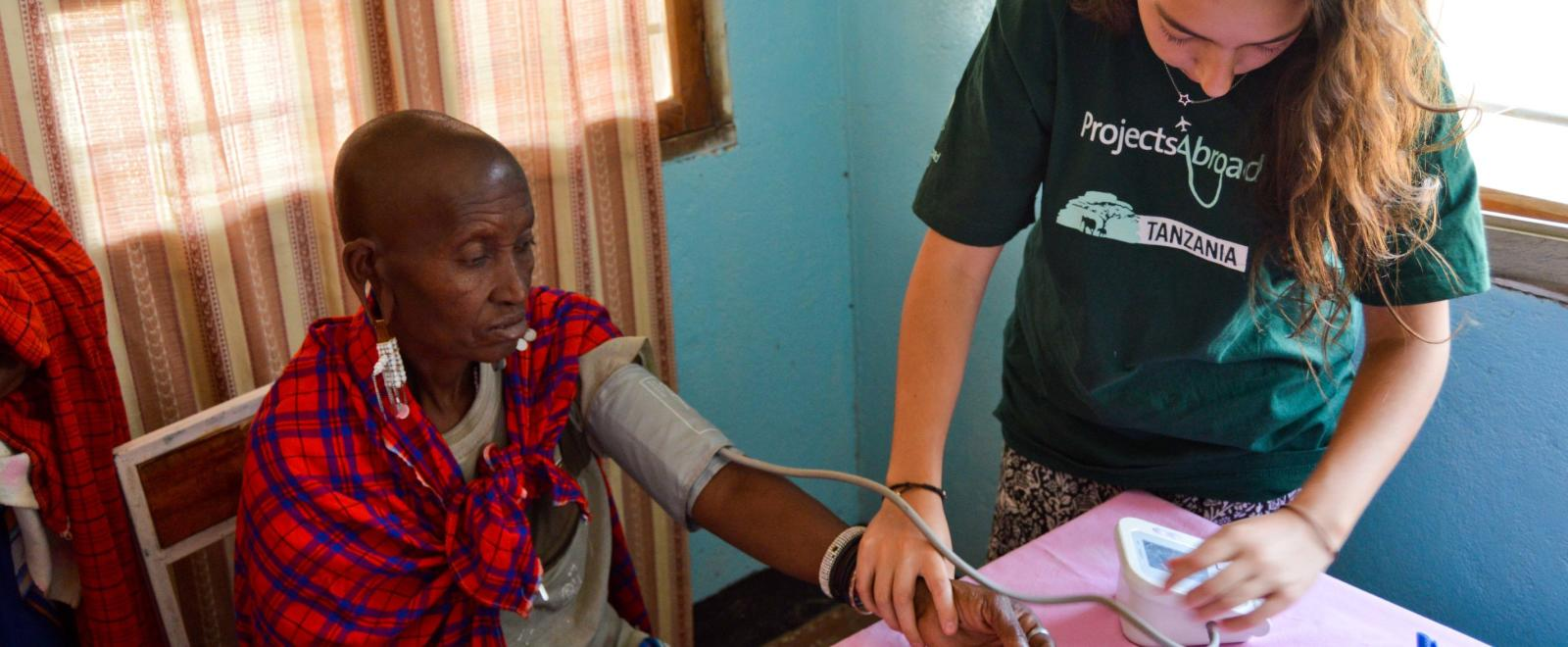 A medical volunteer measures a woman's blood pressure during a community healthcare outreach in Tanzania.